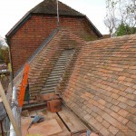 Roof tiling renovations on a grade II listed outbuilding near completion